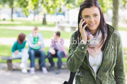 College girl using mobile phone with students in park