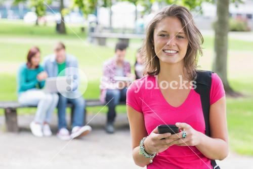 College girl text messaging with blurred students in park