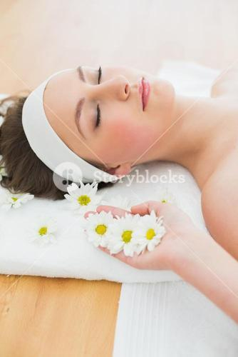 Beautiful woman with eyes closed lying in beauty salon
