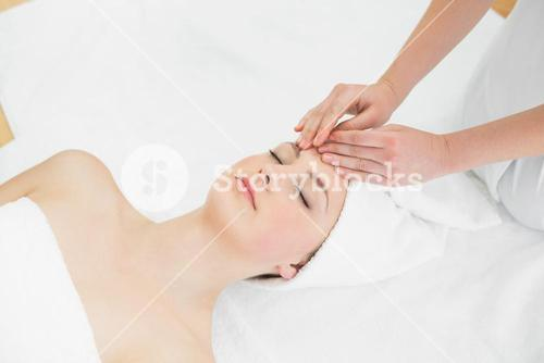 Hands massaging a beautiful womans forehead