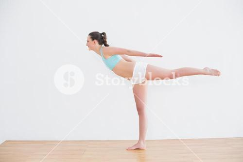 Sporty woman standing on one leg in fitness center