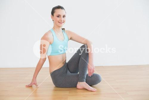 Fit woman sitting in cowface posture in fitness studio