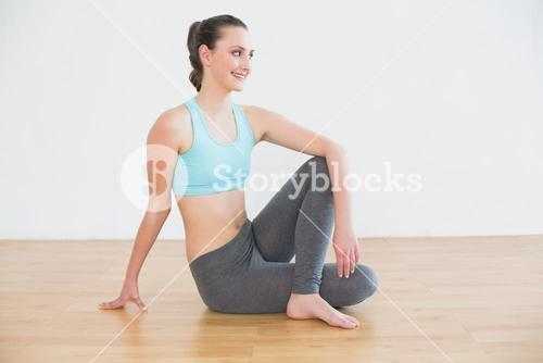 Fit woman in cowface posture in fitness studio