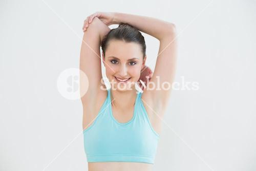 Toned woman stretching hands behind head against wall