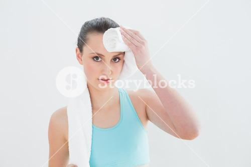 Close up of woman wiping sweat with towel against wall
