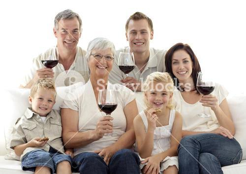 Family in livingroom drinking wine and eating biscuits