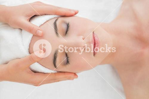 Hands massaging womans forehead at beauty spa