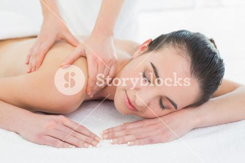 Beautiful woman enjoying back massage at beauty spa
