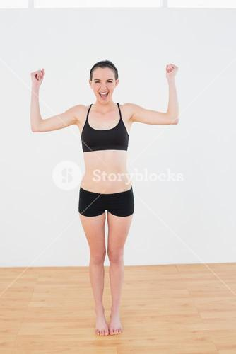 Sporty fit woman clenching fists in fitness studio