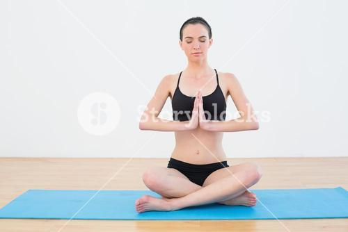 Toned woman with eyes closed sitting in Namaste position at fitness studio