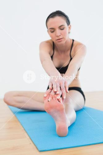 Sporty woman stretching leg in fitness center