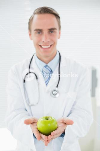 Portrait of a smiling male doctor holding a green apple