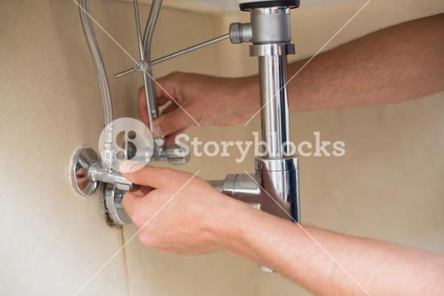 Extreme Close up of a plumbers hands and washbasin drain