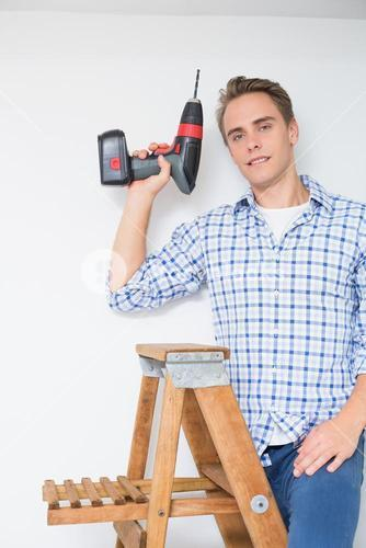 Handyman using cordless drill to the ceiling