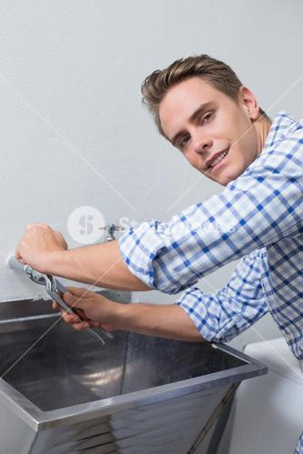 Portrait of plumber fixing water tap with pliers
