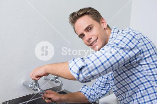 Smiling plumber fixing water tap with pliers