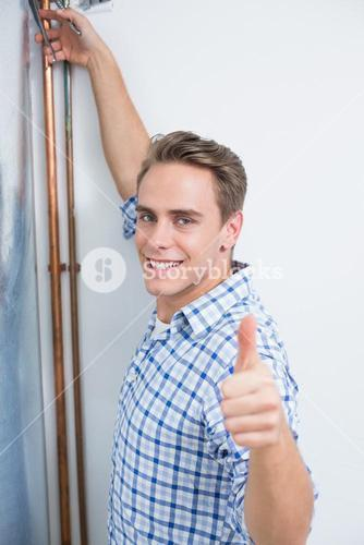 Technician gesturing thumbs up by hot water heater