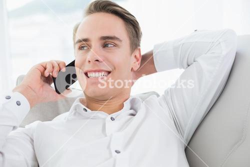 Relaxed young man using cellphone on sofa