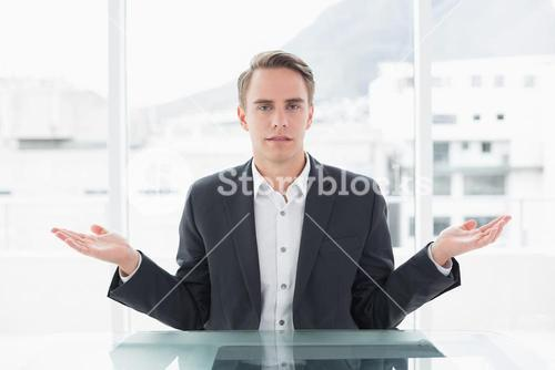 Serious businessman with hand gesture at office desk