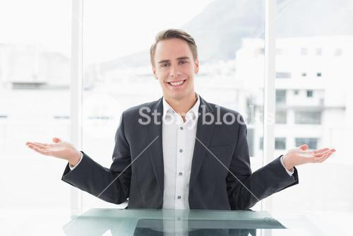 Smiling businessman with hand gesture at office desk