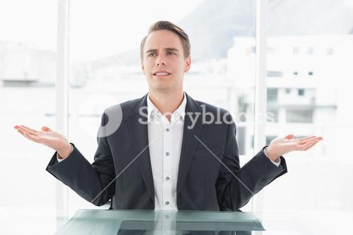 Displeased businessman with hand gesture at office desk
