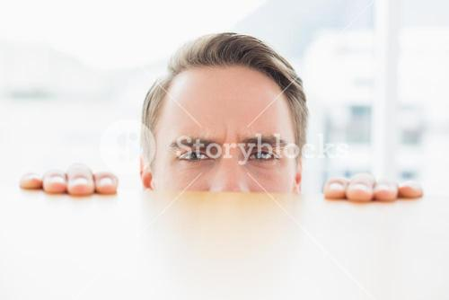 Portrait of businessman looking over blurred wall at office