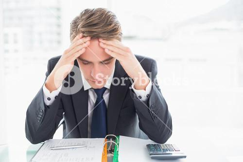 Worried businessman with head in hands at office desk