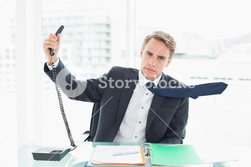Businessman holding out phone at office