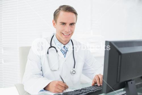 Smiling doctor writing note while using computer at medical office