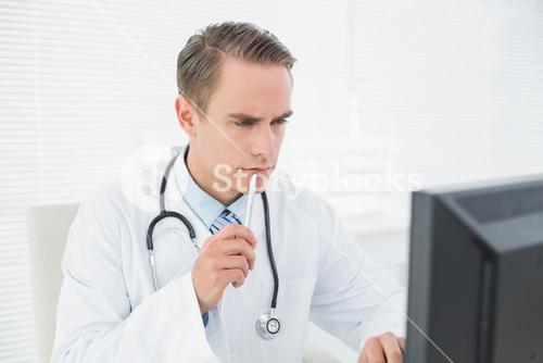 Doctor looking at computer at medical office