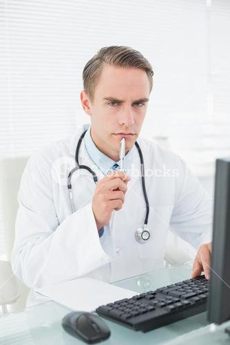 Male doctor using computer at medical office