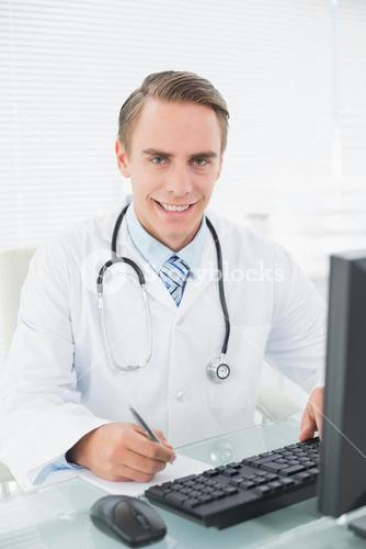 Doctor writing a note while using computer at medical office