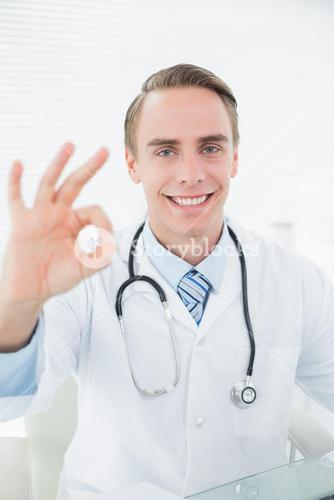 Smiling doctor gesturing okay sign at medical office