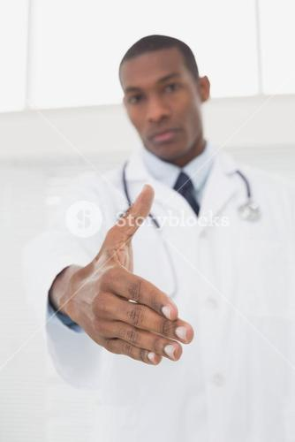Serious male doctor offering a handshake