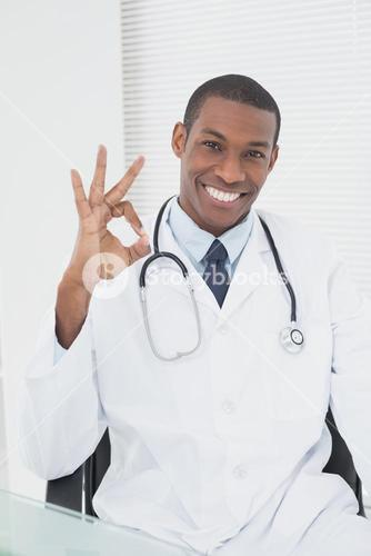 Male doctor gesturing okay sign at medical office