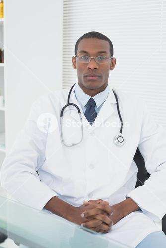 Serious male doctor sitting at medical office