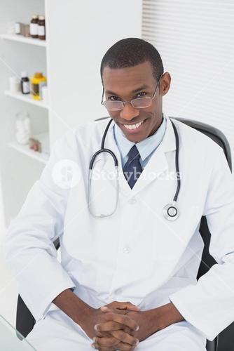 Smiling male doctor sitting at medical office