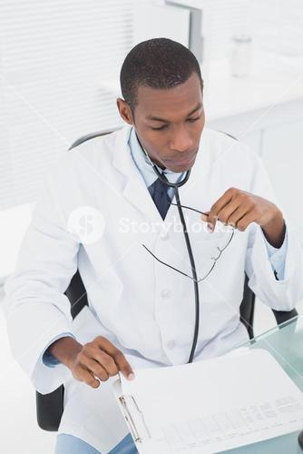 Concentrated doctor reading a note at medical office