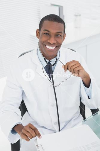 Male doctor sitting at desk in medical office