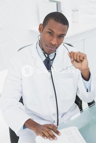 Serious doctor sitting at desk in medical office