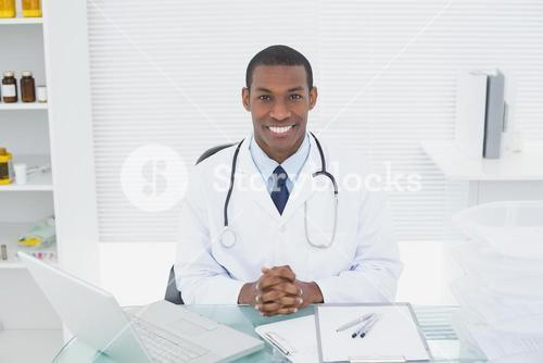 Smiling doctor with laptop at medical office