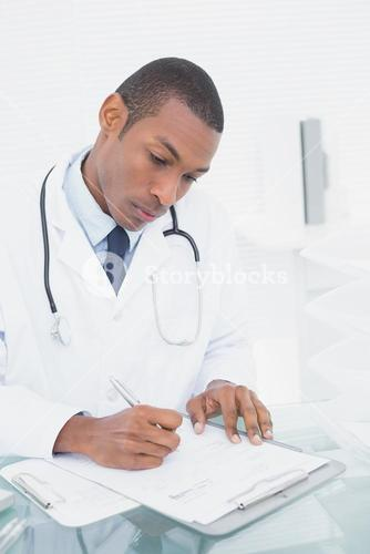 Serious male doctor writing a note