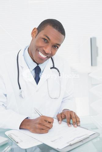 Smiling doctor writing a note at medical office
