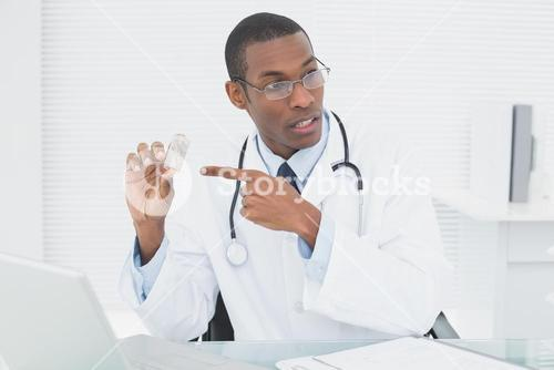 Doctor pointing at prescription bottle in medical office