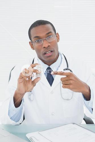 Male doctor pointing at prescription bottle