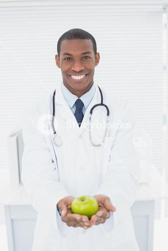 Smiling doctor holding a green apple at medical office
