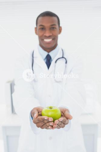 Male doctor holding a green apple at medical office