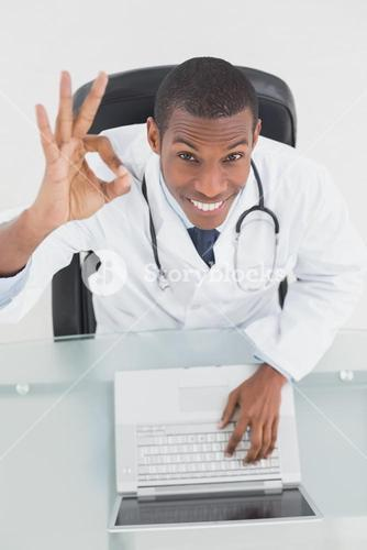 Overhead of a smiling male doctor with laptop gesturing okay sign