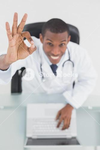 Overhead of a smiling doctor with laptop gesturing okay sign