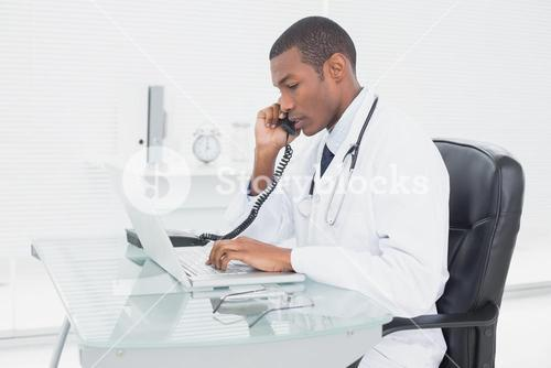 Male doctor using phone and laptop at medical office